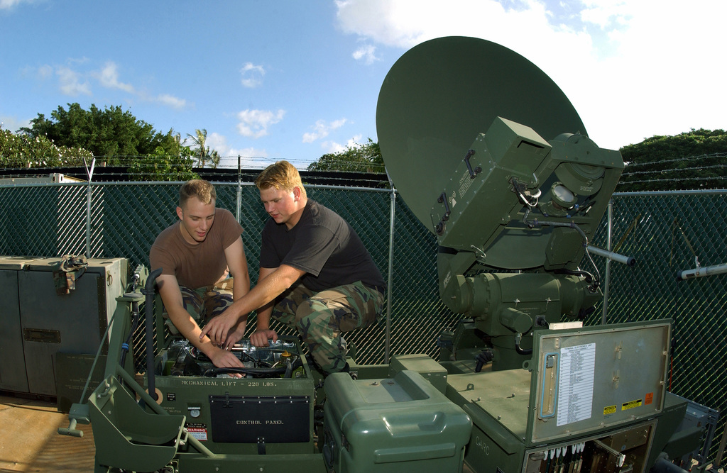 US Air Force (USAF) AIRMAN First Class (A1C) Benjamin Stolz (left) and A1C Phil Cunningham, both assigned to the 15th Communications Squadron (CS) work on the AN/TSC-154 Secure Mobile Anti-Jam Reliable Tactical Terminal (SMART-T), at Hickam Air Force Base (ABF), Hawaii (HI)
