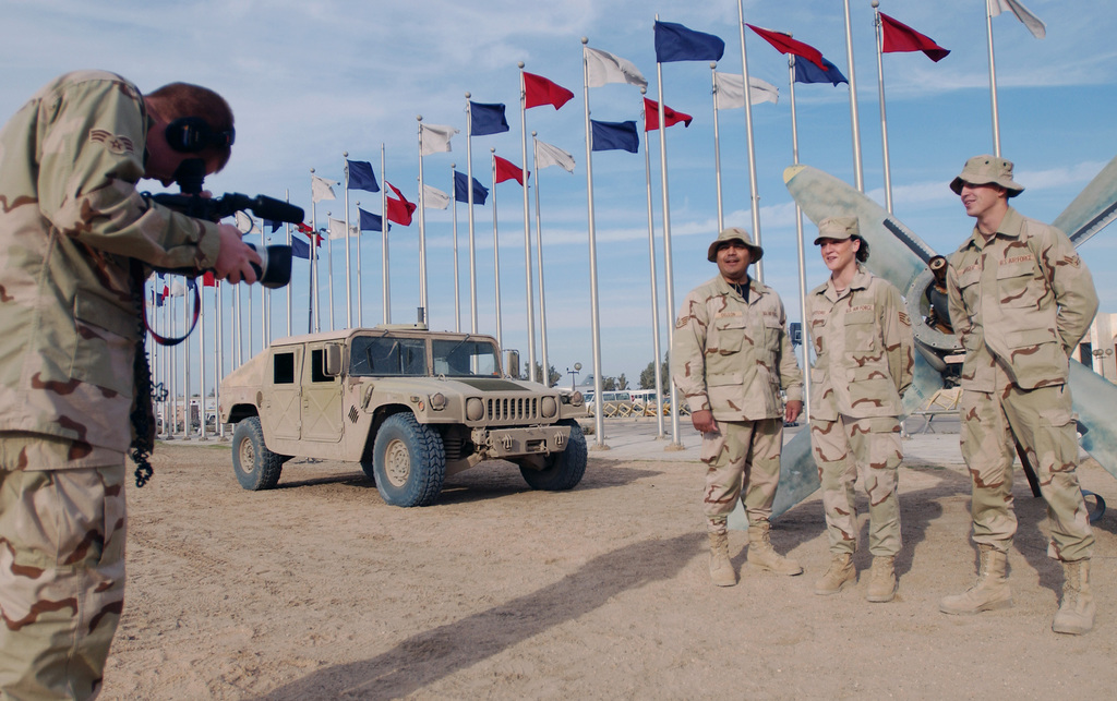 US Air Force (USAF) SENIOR AIRMAN (SRA) Joshua Jasso, Videographer, 447th Expeditionary Communications Squadron (ECS), films Airmen from Kansas deployed to Baghdad International Airport (BIAP), Iraq, for Hometown News Release (HNR) holiday greetings during Operation IRAQI FREEDOM. In the background is a High-Mobility Multipurpose Wheeled Vehicle (HMMWV)