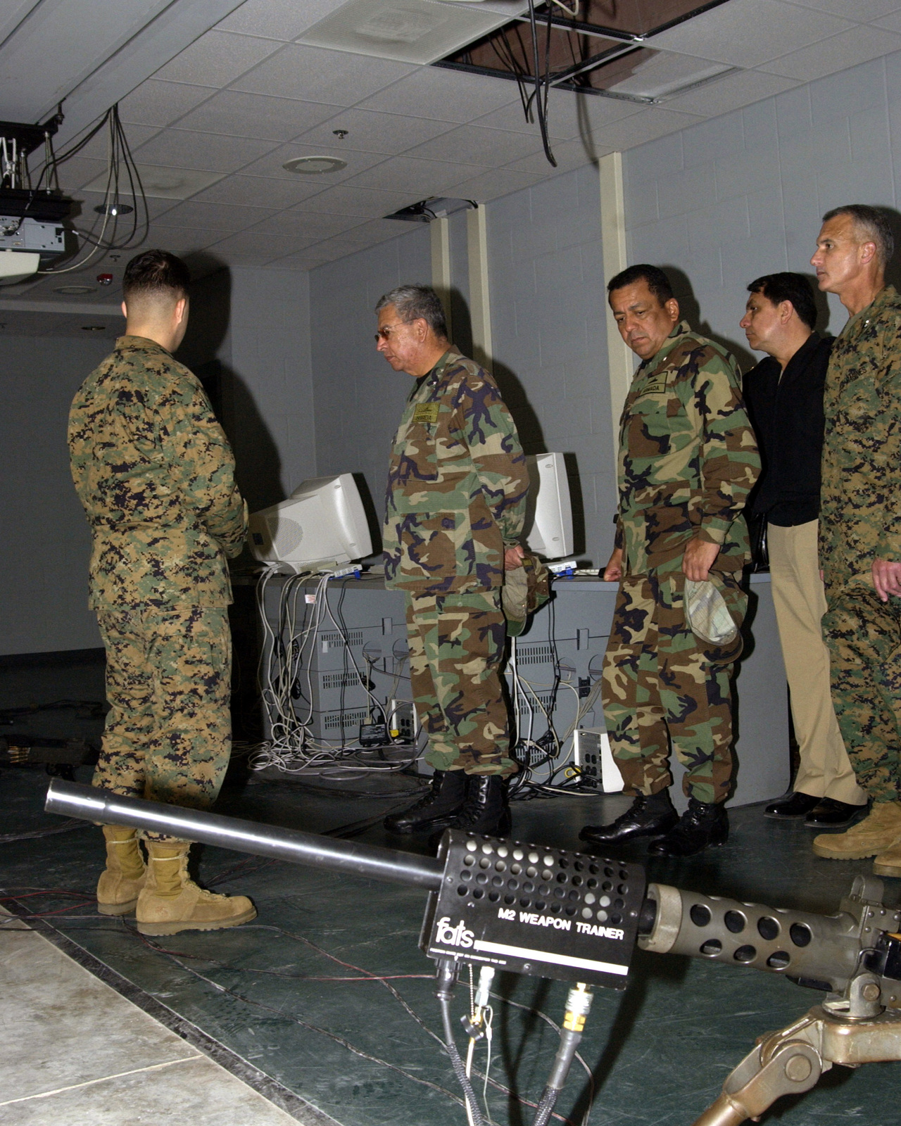 A US Marine Corps (USMC) instructor from the Weapons Field Training Battalion (WFTB) at Marine Corps Recruit Depot (MCRD) Parris Island, South Carolina, briefs the Commandant of the Colombian Marine Corps, Admiral (ADM) Mauricio Soto Gomez, center and Colombian Marine Corps, Sergeant Major (SGMAJ) Guerrero, third from right, on state-of-the-art indoor small arms live fire simulators
