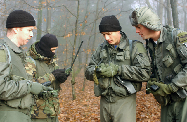 US Air Force (USAF) Fighter Pilots assigned to the 52nd Fighter Wing use their compasses, Global Positioning System (GPS) Units, and ground radios to find the simulated pickup zone during a Combat Certification Training Exercise, held at Spangdahlem Air Base (AB), Germany. Pictured left-to-right are: Captain (CPT) Jonathan Dowty; Major (MAJ) Lee Spechler; CPT Bryan Tash, and CPT Matt Glynn