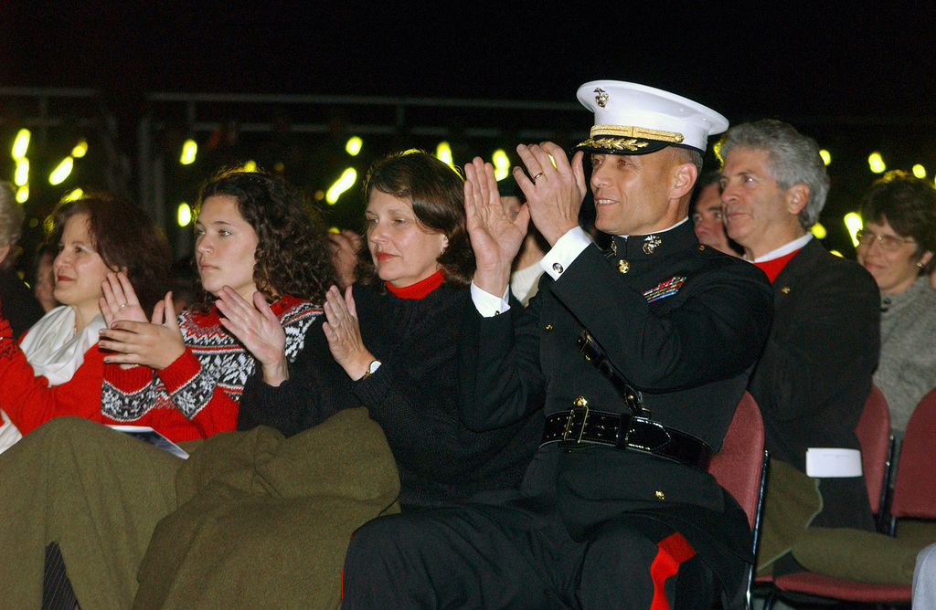 US Marine Corps (USMC) Brigadier General (BGEN) John M. Paxton Jr. Commanding General, Marine Corps Recruit Depot (MCRD) San Diego and the Western Recruiting Region, and guests applaud as the USMC Marine Band San Diego concludes one of the musical selections. The concert is part of the MCRD San Diego, California (CA) Tree Lighting Ceremony