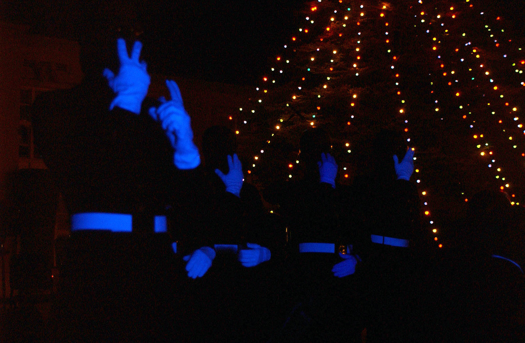 US Marine Corps (USMC) Marine Band San Diego performs a black light version of silent night using sign language at the Marine Corps Recruit Depot (MCRD) San Diego, California (CA), at the annual Tree Lighting Ceremony to celebrate the beginning of the holiday season