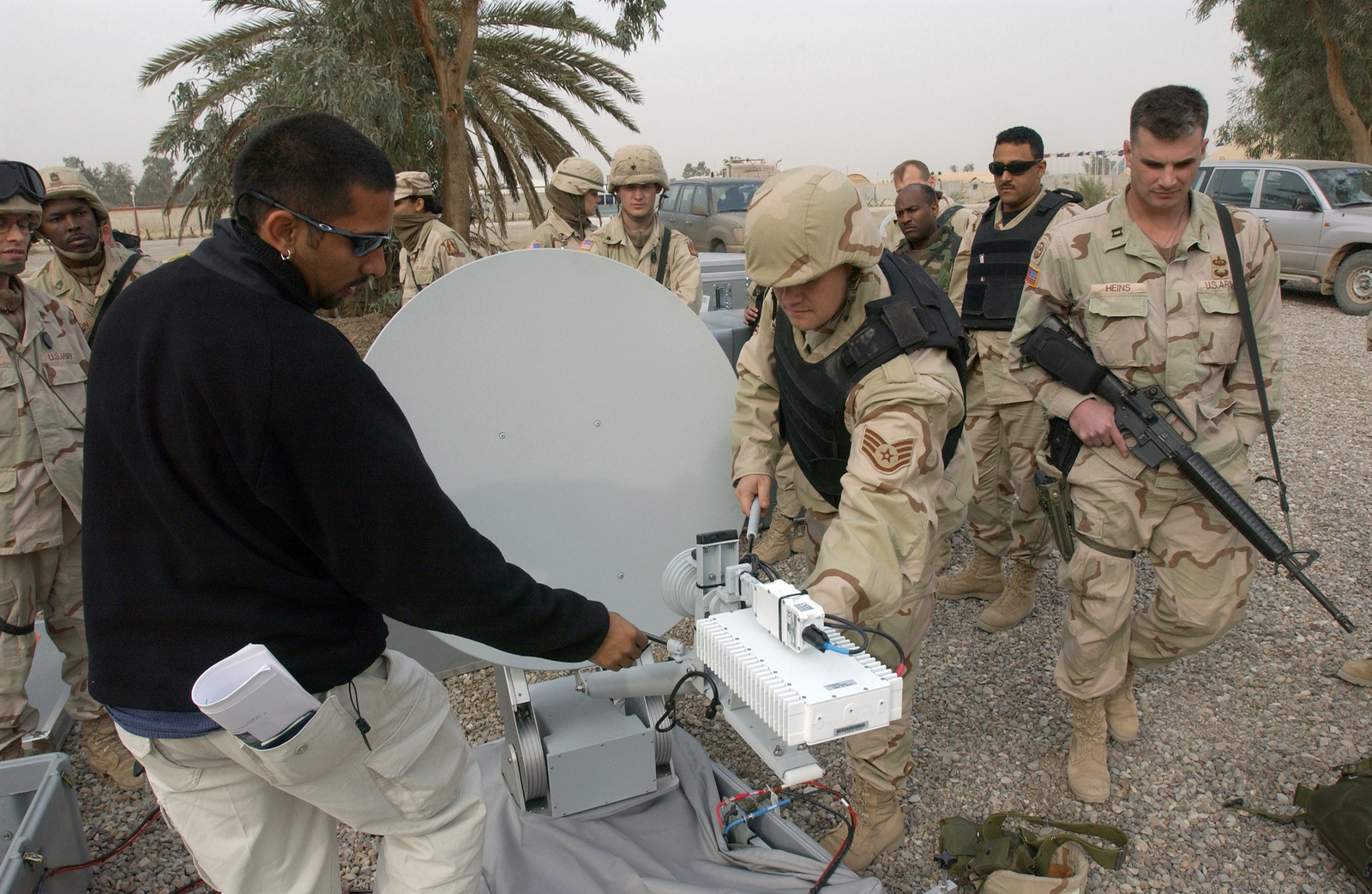 Mr. Reggie Ratcliff and US Air Force (USAF) STAFF Sergeant (SSGT) Ronald VanAusdal, 1ST Combat Camera Squadron (CTCS), Charleston Air Force Base (AFB), South Carolina (SC), teach members of Combat Camera how to attach the 1.2 meter Offset Dish Antenna to the base of the Joint Combat Camera Imagery Transmission Satellite System (JCCITSS) at Baghdad International Airport (BIAP). Members of Combat Camera are in Iraq establishing a satellite imagery management system for deployed teams throughout the theater to transmit photos and video back to a central location during Operation IRAQI FREEDOM