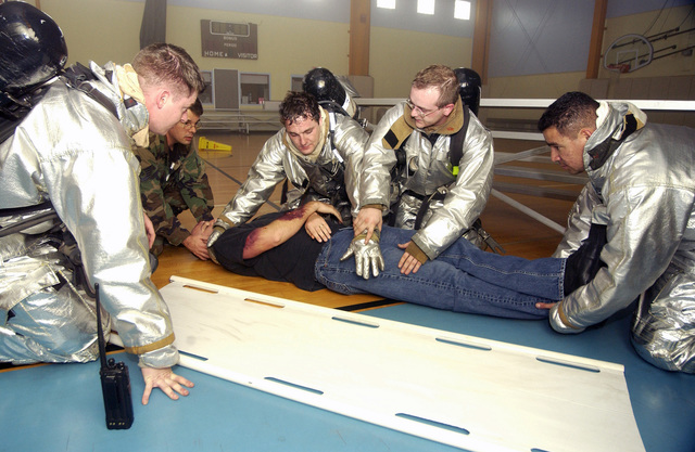 US Air Force (USAF) emergency personnel at Lajes Field, Azores prepare to move a simulated Earthquake victim onto a stretcher during a mass casualty exercise