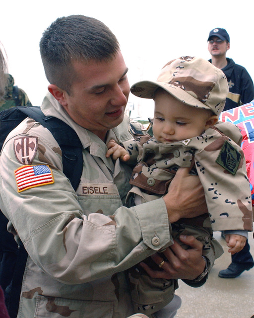 US Army (USA) SPECIALIST First Class (SFC) Randy Eisele, 323rd Military Police Company (MPC), 3rd Platoon (PLT), holds his son for the first time after returning from nearly a years overseas deployment in support of Operation ENDURING FREEDOM