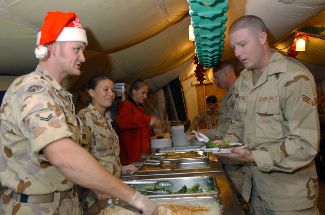 Military members of the Australian Army and Air Force serve dinner to US Air Force (USAF) Airmen at the Baghdad Bistro Dining Facility in Baghdad International Airport (BIAP), Iraq (IRQ). The Australian troops volunteered this service to show their gratitude to the USAF Services that normally maintain dining operations at this Dining Facility during Operation IRAQI FREEDOM