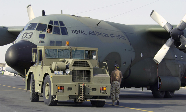 Royal Australian Air Force (RAAF) maintainers from the 36 Squadron, use an aircraft tug to park a RAAF C-130 Hercules on the ramp during Operation IRAQI FREEDOM