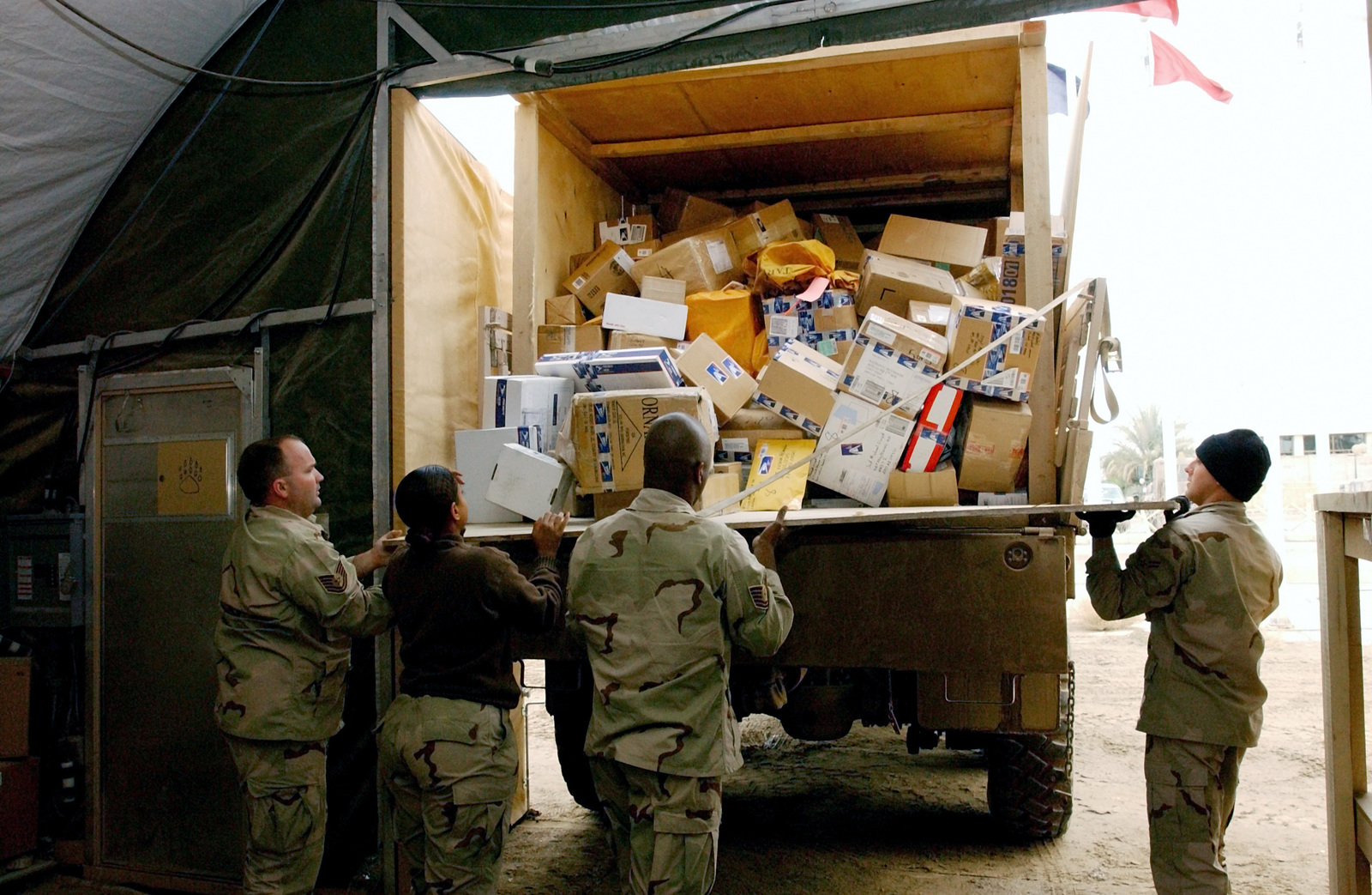 US Air Force (USAF) 447th Expeditionary Communications Squadron (ECS) postal workers offload and sort incoming mail for the unit mail clerks to pick up and distribute to deployed personnel serving at Baghdad International Airport (BIAP), during Operation IRAQI FREEDOM