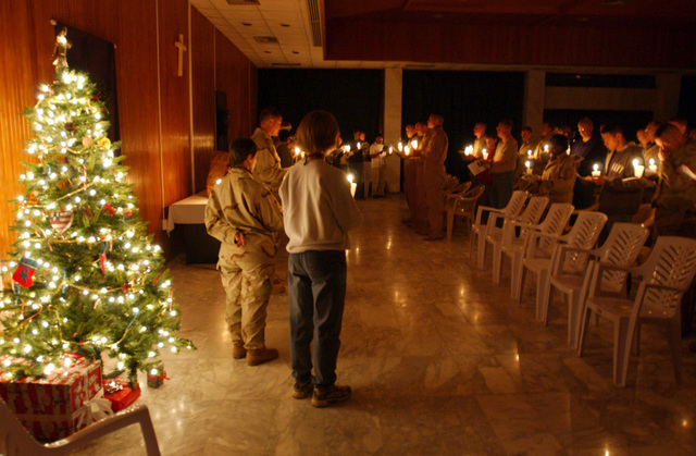 US Air Force (USAF) Airmen of the 447th Air Expeditionary Group (AEG) join in singing Christmas Carols on Christmas Eve as part of the candlelight service during Operation IRAQI FREEDOM. (SUBSTANDARD)