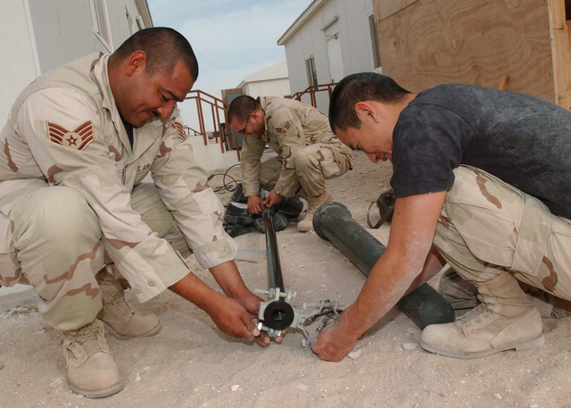 US Air Force (USAF) STAFF Sergeant (SSGT) Juan Lara (left), SENIOR AIRMAN (SRA) Kris Hemberger and AIRMAN First Class (A1C) Gordon Lam (right), Ground Radio Technicians, 379th Expeditionary Communications Squadron (ECS), affix brackets to an antenna prior to installation on the new Operations Group building during Operation IRAQI FREEDOM