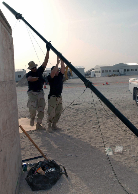 US Air Force (USAF) STAFF Sergeant (SSGT) Juan Lara (left), SENIOR AIRMAN (SRA) Kris Hemberger, Ground Radio Technicians, 379th Expeditionary Communications Squadron (ECS), raise an antenna mast for installation on the new Operations Group building during Operation IRAQI FREEDOM