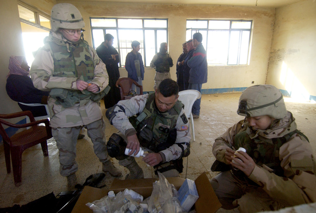US Army (USA) Soldiers from the 173rd Airborne Brigade (ABN BDE), Caserma Ederle, Italy (ITA), sort through and prepare medications for Iraqi patients in a temporary medical clinic set up in a small Iraqi primary school during Operation IRAQI FREEDOM