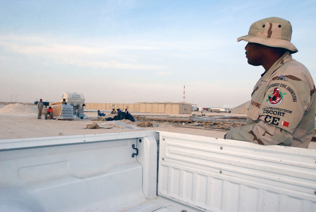 US Air Force (USAF) AIRMAN First Class (A1C) Daryll Brandford, escort for third country national workers, 379th Expeditionary Civil Engineer Squadron (ECES), observes the workers at a dig site on the base during Operation IRAQI FREEDOM