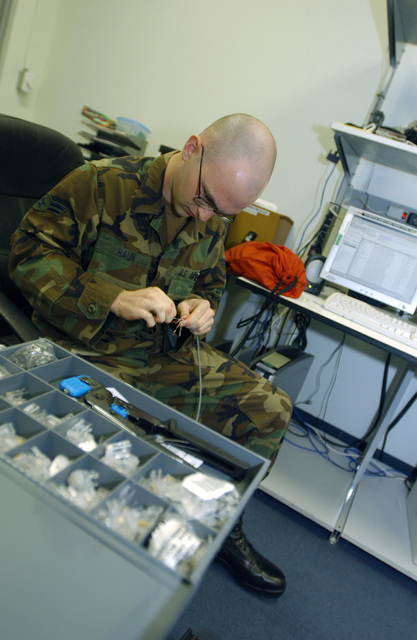 US Air Force (USAF) AIRMAN First Class (A1C) Samuel Haun, 40th Expeditionary Communications Flight, splices a cable in preparation for a RJ-45 connector to create a Local Area Network (LAN) cable to connect many computer stations to one central network during Operation IRAQI FREEDOM