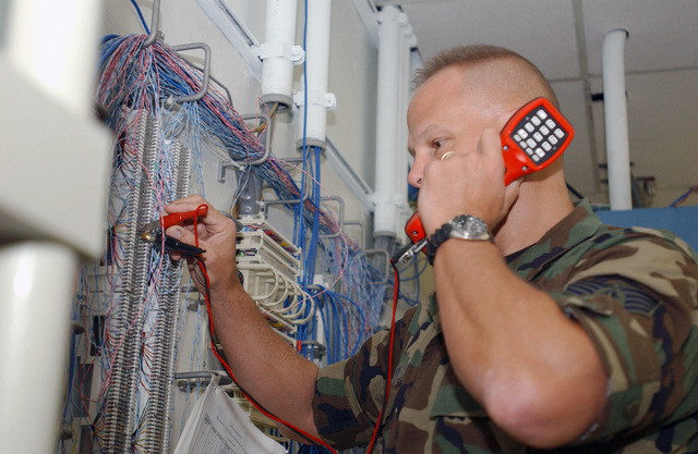 US Air Force (USAF) STAFF Sergeant (SSGT) Eric Scurry, 40th Expeditionary Communications Flight (ECF), uses a Harris TS21 buttset hooked to a 66 block to test the phone lines during Operation IRAQI FREEDOM