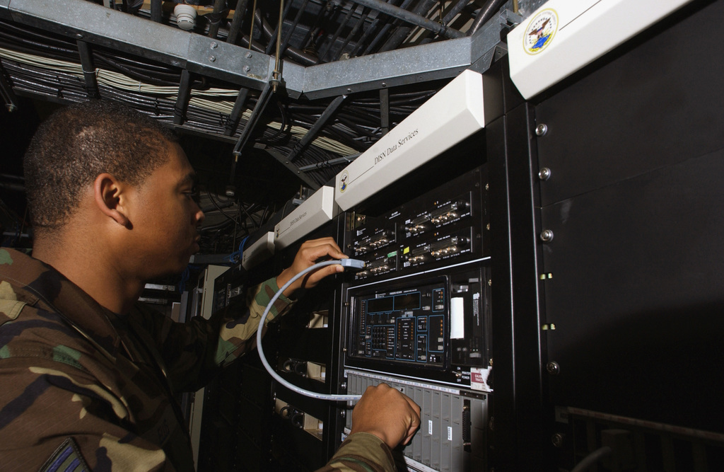 US Air Force (USAF) SENIOR AIRMAN (SRA) Jaris Ellis, 786th Communications Squadron (CS), installs a Internet Protocol Router (IPR) while checking the performance of a Bit Error Rate (BER) tester used to test the accuracy of incoming data