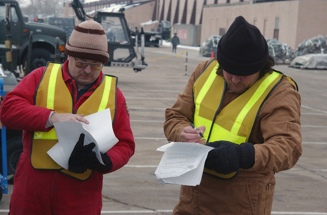 Mr. Dave Farley, Videographer, 55th Communications Squadron (CS), Offutt Air Force Base (AFB), Nebraska (NE), and Mr. Anthony Anderson, Aircraft Mechanic, 55th Maintenance Squadron (MXS), review their cargo inventory sheets during chalk processing during an Operational Readiness Exercise (ORE). Over a two-week period, the 55th Wing (WG) is conducting an ORE in preparation for an upcoming Air Combat Command (ACC) Operational Readiness Inspection (ORI) in March