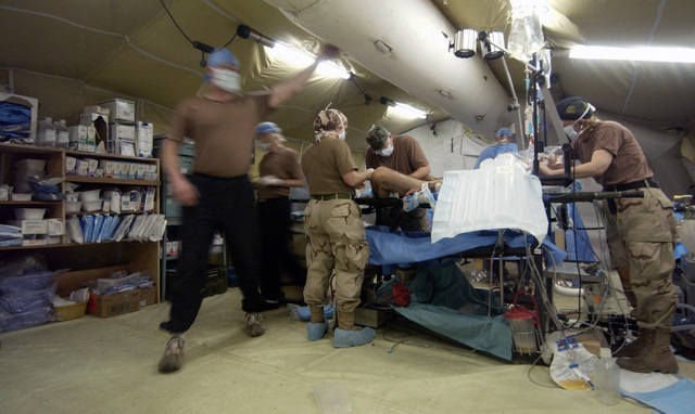 US Army (USA) Soldiers of the 250th Forward Surgical Team (FST) (Airborne), Fort Lewis, Washington (WA), scramble to perform emergency treatment for two Iraqi civilians caught in a blast, set by insurgents, outside the gates of Kirkuk Air Base (AB), Iraq, during Operation IRAQI FREEDOM