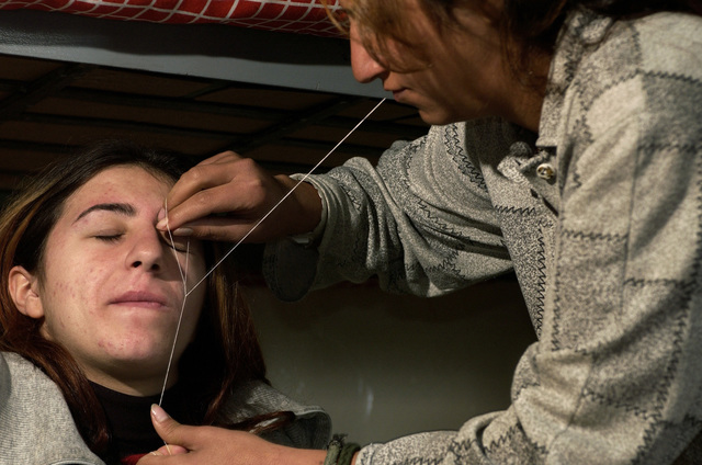 Cell Commander Trustee, Dayla Mansor, uses a traditional method as she plucks an inmates eyebrows using string from a pillowcase at the Rusafa Prison Complex, Iraq, during Operation IRAQI FREEDOM