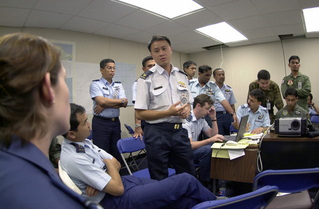 Major Francis Ngooi Choong Ngee, Air Operations Department, Singapore confirms air drop data presented by FLGOFF (Flying Officer) Melissa Dalby, 86 Wing (WG), Royal Australian Air Force, during PACIFIC AIRLIFT RALLY 2001.  PACIFIC AIRLIFT RALLY (PAR) is a PACAF-sponsored military airlift symposium for countries in the pacific region.  PAR is held every two years and is hosted by a pacific nation.  This year Andersen AFB, Guam is the host nation.  The symposium includes informational seminars with area of expertise briefings, a command post exercise (CPX) which addresses military airlift support to a humanitarian airlift/disaster relief scenario, and a concurrent flying training program ...