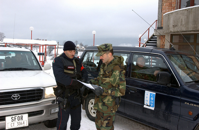 US Navy (USN) Commander (CDR) Toth (right), Stabilization Force (SFOR) Bosnia, speaks with the Italian Multinational Support Unit (MSU) Commander as he prepares to search for war criminal Rodovan Karadjic in the town of Pale during Operation JOINT FORGE