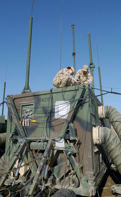 US Air Force (USAF) AIRMAN First Class (A1C) Elizabeth Cordell, left and SENIOR AIRMAN (SRA) Richard Robbins, from the 447th Expeditionary Air Control Squadron (EACS), maintain antennas on Camp Griffin at Baghdad International Airport (BIA), Iraq, in support of Operation IRAQI FREEDOM