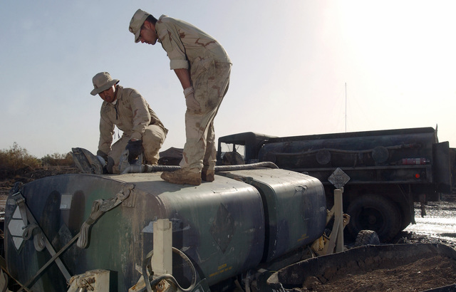 US Air Force (USAF) AIRMAN First Class (A1C) Lawrence Genova, right and A1C Joshua Serna, with the 447th Expeditionary Air Control Squadron (EACS), Electrical Power Production, refuel a generator on Camp Griffin at Baghdad International Airport (BIA), Iraq, in support of Operation IRAQI FREEDOM
