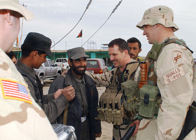 US Army (USA) Private First Class (A1C) Ronnie M. George, left, Major (MAJ) Alva Lee Cook and SPECIALIST (SPC) Kyle R. Qualls, right, all from the 486th Civil Affairs Reserve Battalion (CARB) meet with Afghani policemen