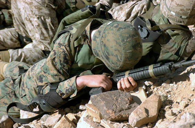 US Marine Corps (USMC) Private First Class (PFC) Joshua Harison, 1ST Battalion, 2nd Marines (1/2), Bravo Company (B CO), 2nd Platoon (PLT), takes cover, protecting his 5.56 mm M16A2 rifle, as a shoulder fired rocket launcher goes off over ridge he and his squad are using as cover during a live fire exercise at Range 400 Marine Air Ground Task Force Training Command (MAGTF-TC), Twentynine Palms, California (CA)