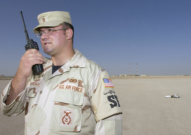 US Air Force (USAF) STAFF Sergeant (SSGT) Wayne Holliday, with the 379th Expeditionary Security Forces Squadron (ESFS), radios the air traffic control tower for permission to launch a Desert Hawk surveillance system at a forward-deployed location in support of Operation IRAQI FREEDOM
