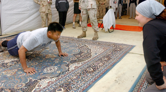 US Air Force (USAF) Technical Sergeant (TSGT) Glen Primero, performs 85-push-ups as his teammate STAFF Sergeant (SSGT) Stacy Pearsall cheers him on during the 447th Air Expeditionary Group (AEG) Sports Day at Baghdad International Airport (BIA), during Operation IRAQI FREEDOM