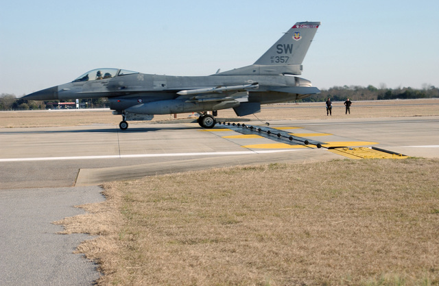 A US Air Force (USAF) F-16 Fighting Falcon fighter assigned to Shaw Air Force Base (AFB), South Carolina (SC), hooks an arresting cable during a certification test. In an emergency, a barrier cable is used to catch and stop an aircraft