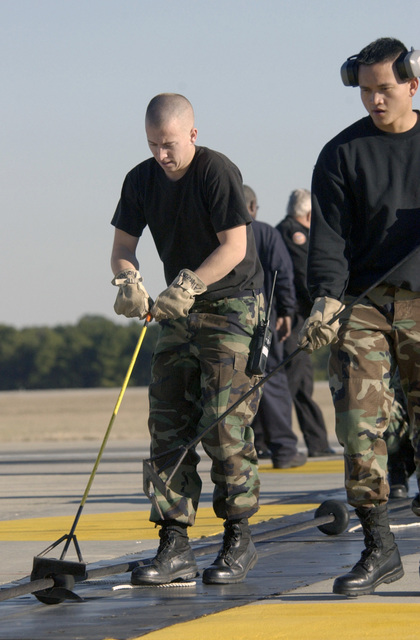 US Air Force (USAF) AIRMAN First Class (A1C) Brandon Albrecht, left and A1C Raymond Drury, both fire protection specialists assigned to the 20th Civil Engineering Squadron (CES), Shaw Air Force Base (AFB), South Carolina (SC), reset an arresting cable on the runway following a certification test. A barrier engagement is a process that involves the use of a cable to catch and stop an aircraft during an emergency landing