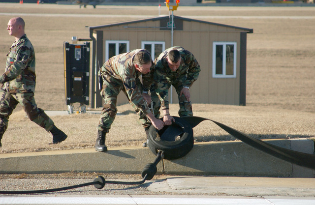 US Air Force (USAF) Fire protection specialists assigned to the 20th Civil Engineering Squadron (CES), Shaw Air Force Base (AFB), South Carolina (SC), reset an arresting cable on the runway following a certification test. A barrier engagement is a process that involves the use of a cable to catch and stop an aircraft during an emergency landing