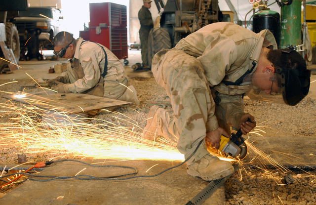 US Air Force (USAF) STAFF Sergeant (SSGT) Michael Batres, left and AIRMAN First Class (A1C) Michael Davis, with the 447th Expeditionary Logistical Readiness Squadron (ELRS), both Special Purpose Vehicle Mechanics, carefully weld steel plates for a 5-ton truck as armor protection, at the Baghdad International Airport (BIA), Iraq, in support of Operation IRAQI FREEDOM