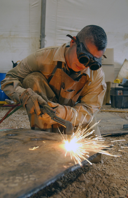 US Air Force (USAF) STAFF Sergeant (SSGT) Michael Batres, with the 447th Expeditionary Logistical Readiness Squadron (ELRS), a Special Purpose Vehicle Mechanic, carefully welds a steel plate for a 5-ton truck as armor protection, at the Baghdad International Airport (BIA), Iraq, in support of Operation IRAQI FREEDOM