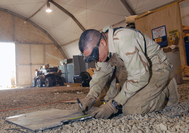 US Air Force (USAF) STAFF Sergeant (SSGT) Michael Batres, with the 447th Expeditionary Logistical Readiness Squadron (ELRS), a Special Purpose Vehicle Mechanic, carefully measures a steel plate for a 5-ton truck as armor protection, at the Baghdad International Airport (BIA), Iraq, in support of Operation IRAQI FREEDOM