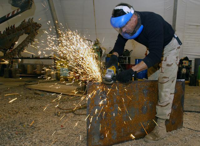US Air Force (USAF) Technical Sergeant (TSGT) Mark Sauerwald, with the 447th Expeditionary Logistical Readiness Squadron (ELRS), a Special Purpose Vehicle Mechanic, grinds a steel plate to be fitted onto a 5-ton truck for armor protection at Baghdad International Airport (BIA), Iraq, in support of Operation IRAQI FREEDOM