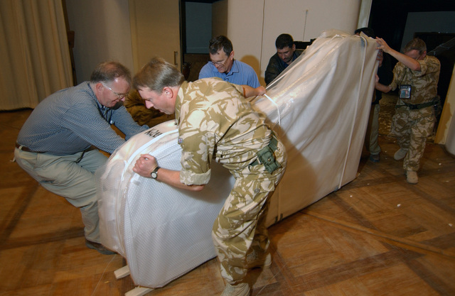 Royal British Army (RBA) Lieutenant Colonel (LCOL) Philip Thorp, a volunteer from the Coalition Provisional Authority (CPA), helps deliver a donated Steinway piano to the Iraq National Symphony Orchestra at the Baghdad Convention Center, Baghdad, Iraq, during Operation IRAQI FREEDOM