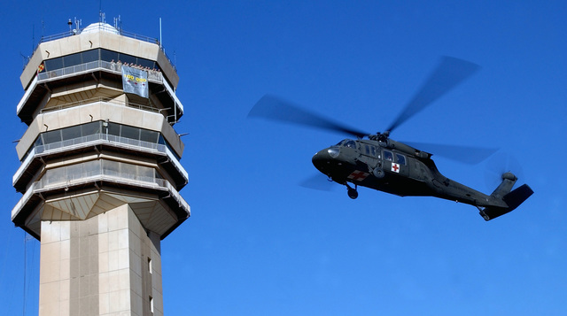 As a US Army (USA) UH-60Q Black Hawk Medical Evacuation (MEDEVAC) helicopter approaches, personnel from the Australian Air Control Tower Detachmet, Task Unit 633.4.2 celebrate the One Hundred Thousand aircraft to move through Baghdad International Airport (BIA), Iraq, in support of Operation IRAQI FREEDOM