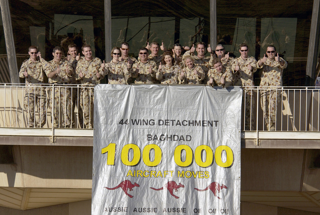 Austrailian military personnel from the Australian Air Control Tower Detachmet, Task Unit 633.4.2 celebrate the One Hundred Thousand aircraft to move through Baghdad International Airport (BIA), Iraq, in support of Operation IRAQI FREEDOM
