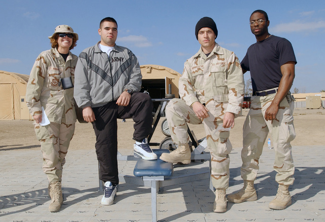 Left to right, US Air Force (USAF) Major (MAJ) Tamara Rogers, US Army (USA) Private First Class (PFC) Randy Zarate, USAF SENIOR AIRMAN (SRA) Nathan Morningstar, and AIRMAN First Class (A1C) Randy Ellis, stand victoriously following a bench press competition at Baghdad International Airport (BIA), Iraq, during Operation IRAQI FREEDOM