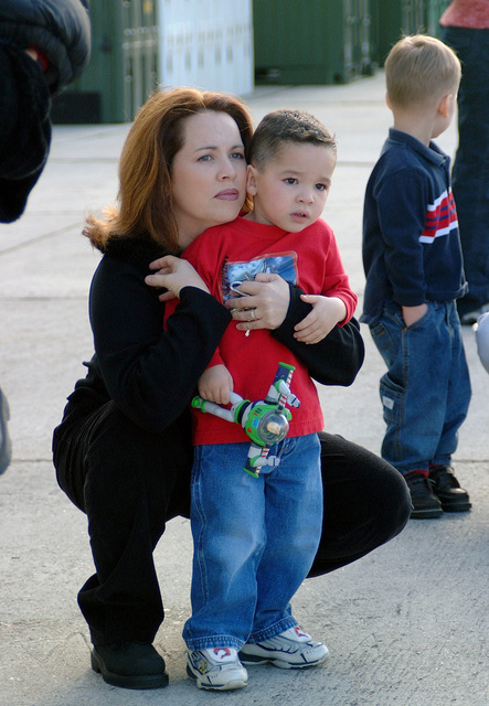 Michelle Ortiz and her son, Alistair Ortiz Jr., on the ramp at Marine Corps Air Station (MCAS) Beaufort, South Carolina (SC), look for her husband, US Marine Corps (USMC) GUNNERY Sergeant (GYSGT) Alistair Ortiz, to deplane along with other Marines after their routine six-month deployment