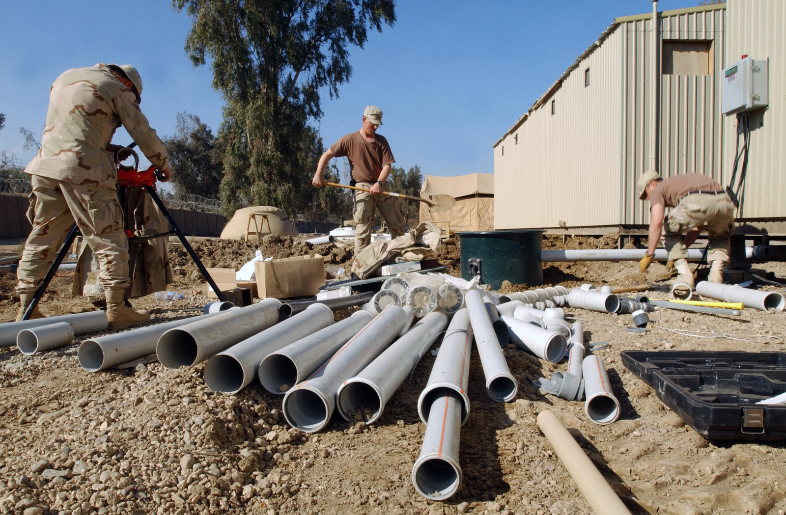 US Air Force (USAF) 447th Expeditionary Civil Engineer Squadron (ECES), Utility Systems Specialists install a grinder on newly installed portable latrines at Baghdad International Airport (BIA), Iraq (IRQ), in support of Operation IRAQI FREEDOM