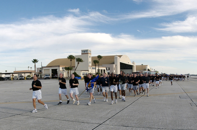 """US Air Force (USAF) Colonel (COL) Tanker Snyder, Commander (CO) of the 6th Air Mobility Wing (AMW) (bottom left), leads the base wing and tenant unit personnel on a """"Fit to Fight"""" 2 mile run on the flight line"""
