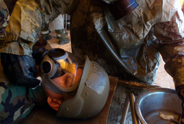 US Air Force (USAF) AIRMAN First Class (A1C) Amory Saucedo, with the 355th Expeditionary Medical Squadron (EMS), lays quietly as a member of the decontamination team remove simulated chemicals he has been exposed to in his Mission-Oriented Protective Postures level 4 (MOPP-4) gear, during Exercise Bushwhacker 03-04 at Davis-Monthan Air Force Base (AFB), Arizona (AZ)