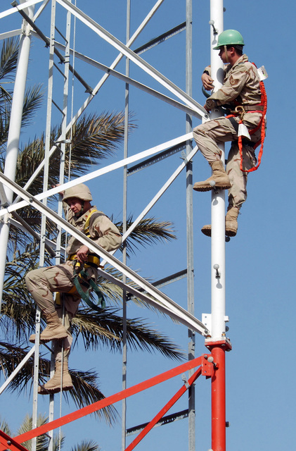 US Air Force (USAF) Major (MAJ) Jon Petruzzi, left, the 447th Expeditionary Communications Squadron (ECS) Commander and STAFF Sergeant (SSGT) Jason Bulgin, a Cable Antenna Maintenance SPECIALIST, climb to the top of a 120-ft tall radio tower at Baghdad International Airport (BIA), Iraq (IRQ), in support of Operation IRAQI FREEDOM