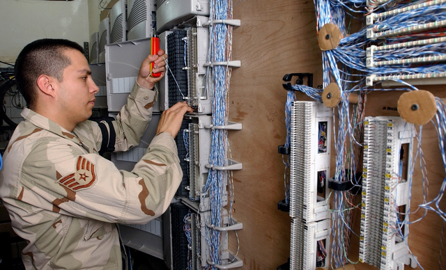 US Air Force (USAF) STAFF Sergeant (SSGT) Ernesto Figueroa with the 7th Expeditionary Communications Squadron (CS), works on the Main Distributions Frame installing phone lines at the Baghdad International Airport (BIA), in support of Operation IRAQI FREEDOM