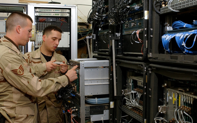 US Air Force (USAF) STAFF Sergeant (SSGT) Nathan Haley, left and SENIOR AIRMAN (SRA) Kenneth Merkel perform a Preventative Maintenance Inspection (PMI) on the Basic Access Modules System (BAMS), on the Main Distributions Frame at the Baghdad International Airport (BIA), in support of Operation IRAQI FREEDOM