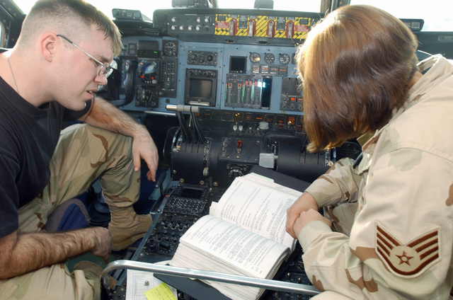 US Air Force (USAF) STAFF Sergeant (SSGT) William Thompson III, a Guidance Control SPECIALIST and SSGT Raquel Ferrel, both C-5 Galaxy aircraft Crew Chiefs with the 447th Aircraft Maintenance Squadron (AMXS), review an avionics maintenance Technical Order (TO) at the Baghdad International Airport (BIA), Iraq (IRQ), in support of Operation IRAQI FREEDOM